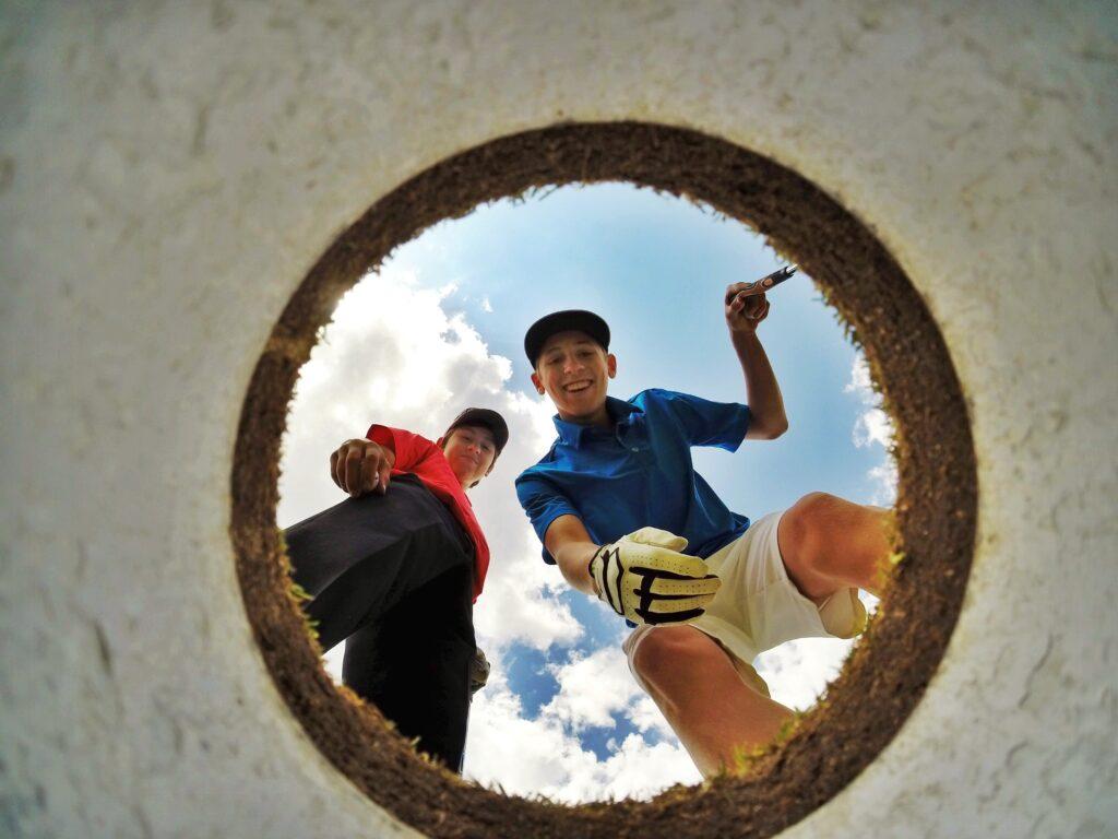 ホールを見て笑みを浮かべる2人のゴルファー