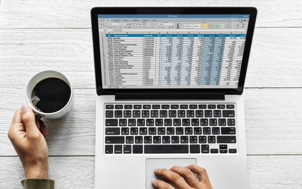 数値表が映るパソコンとコーヒーカップ
