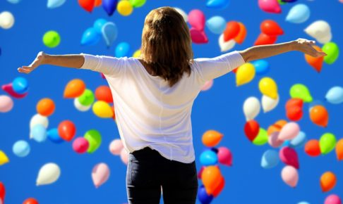 たくさんの風船の前で手を広げる女性