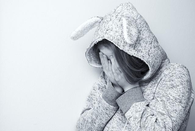 顔を抑える、ウサギのパーカーを着た女性