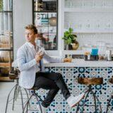 カフェでスマホ片手に誰かを待つ男性