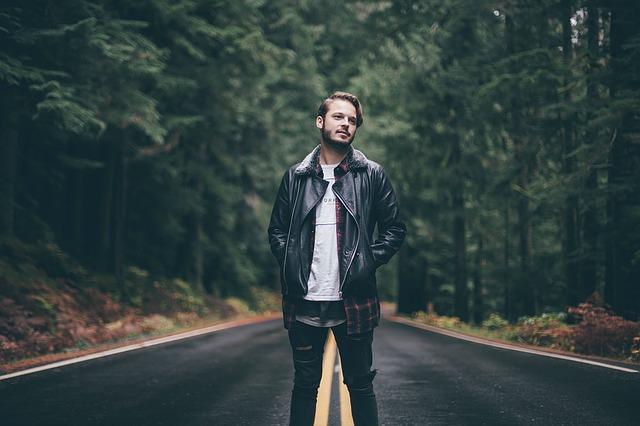 森の中にある道路に立つ男性