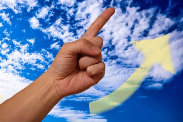 空を背景にして上を指さす