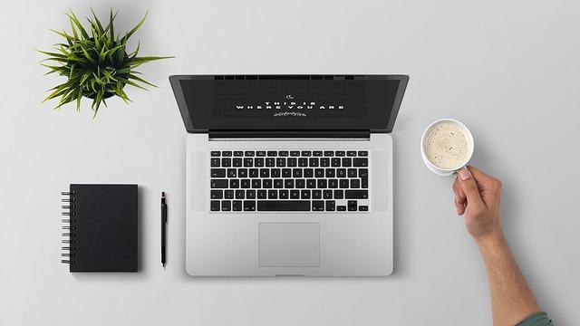 パソコンとコーヒーとノートとペンと植物