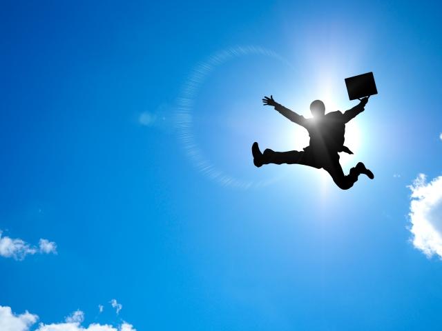 空に高くジャンプするビジネスマンのシルエット
