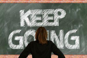 KEEP GOINGと書かれた黒板の前に立つ女性