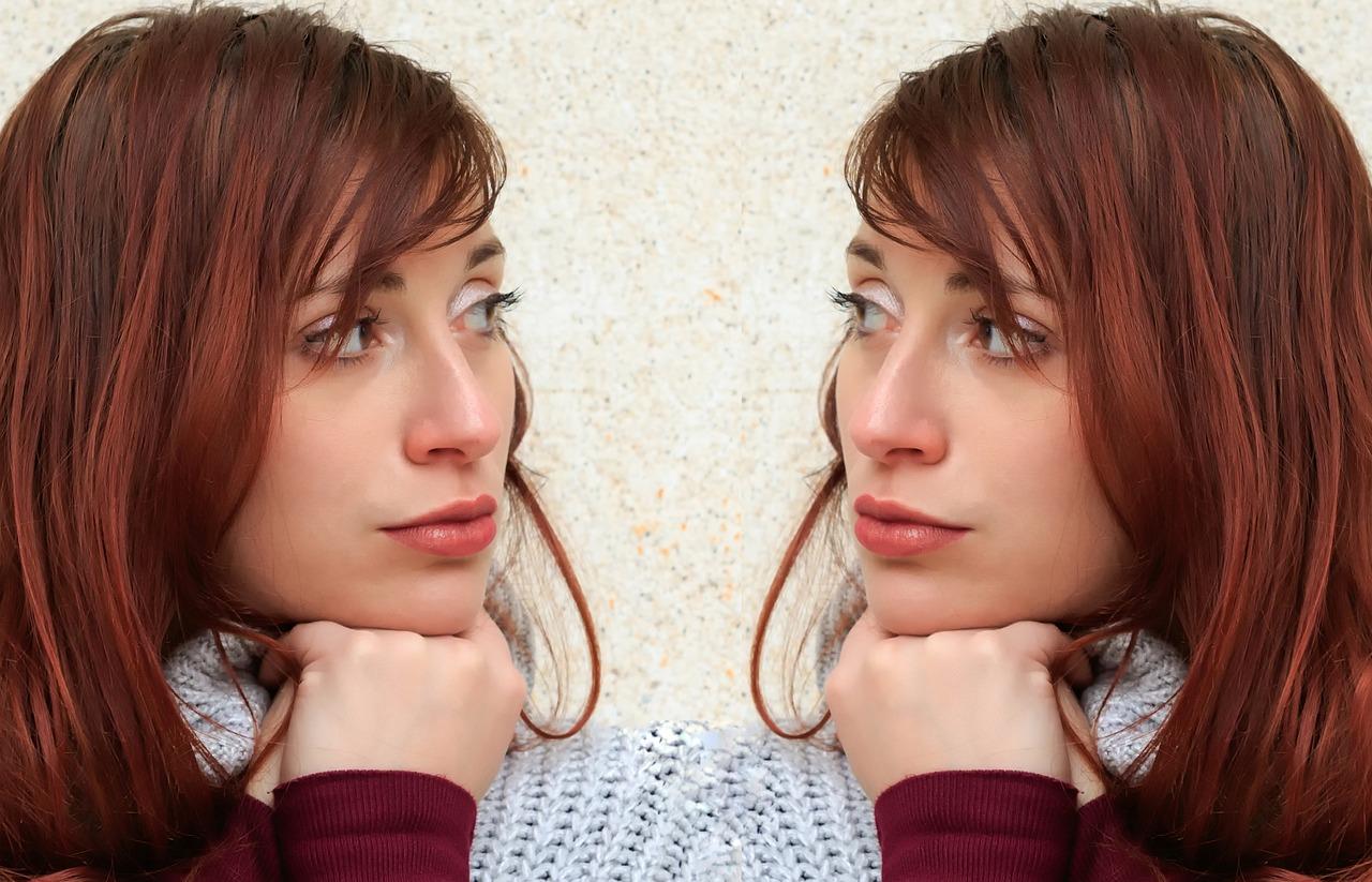 顎に手を添える女性の鏡映し