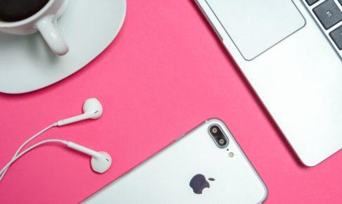 ピンク柄のテーブルに置かれた、コーヒーカップとパソコンとiphone