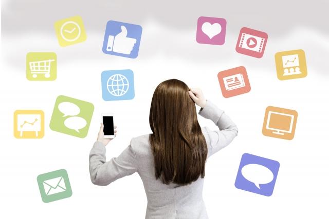 様々なアプリを入れたスマホを持って評価を気にする女性