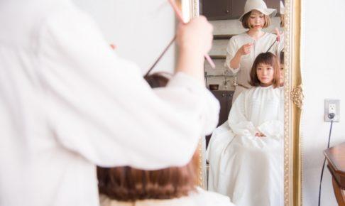 美容院で髪を切ってもらう女性