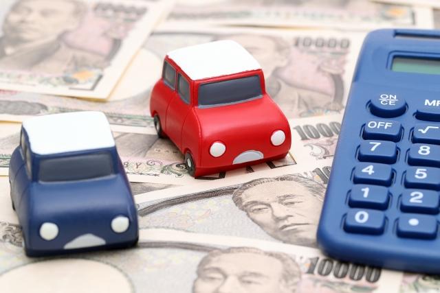 おもちゃの自動車と電卓と1万円