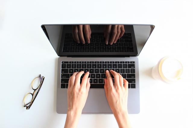 パソコンを操作する手と眼鏡とコーヒーカップ
