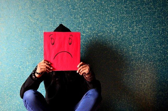 不満な顔が描かれた赤いプレートを持つ人