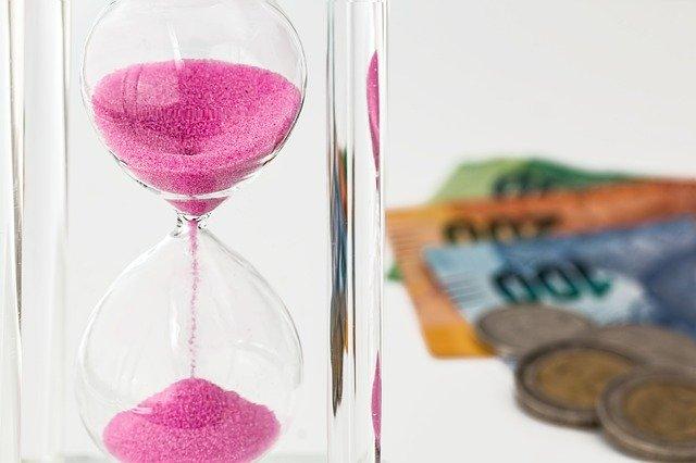 ピンクの砂時計と外国紙幣と硬貨