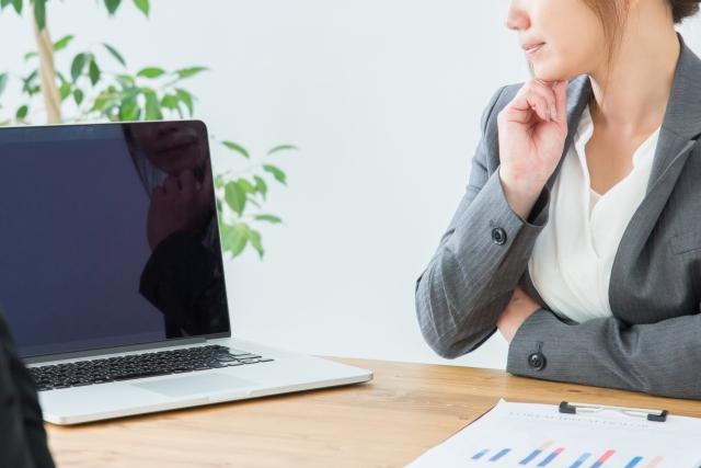 ノートパソコンを見つめて考える女性