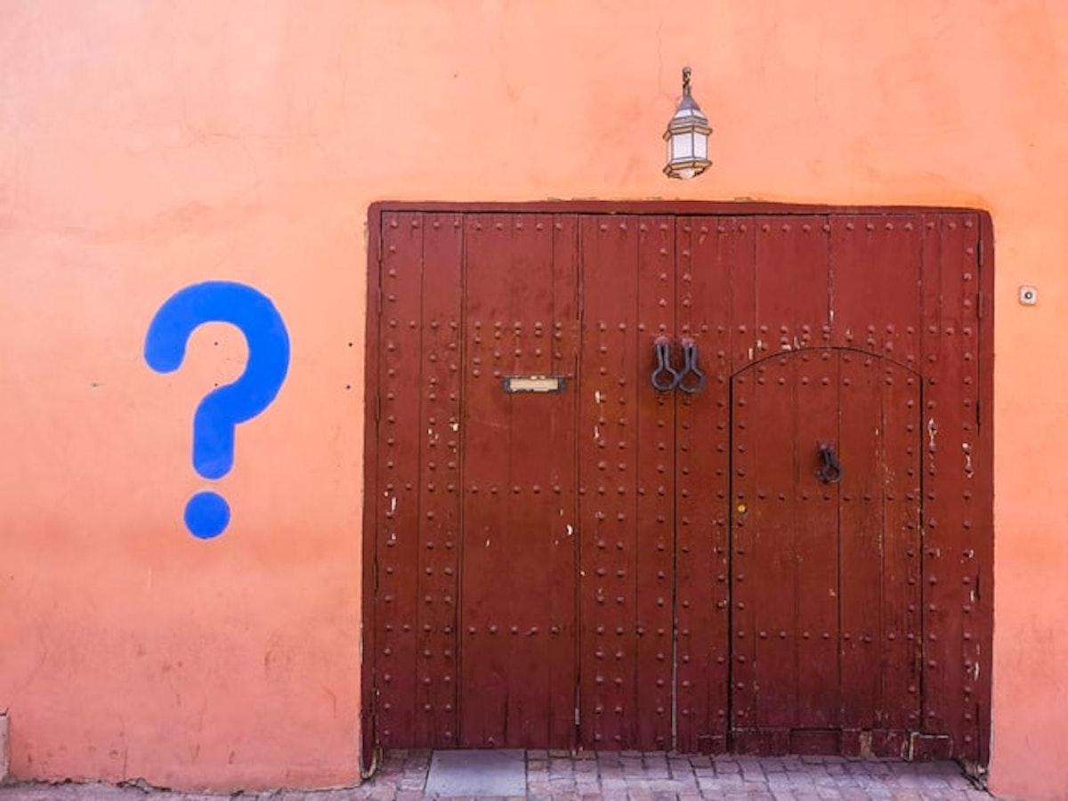 洋風の壁とドアに書かれたクエスチョンマーク