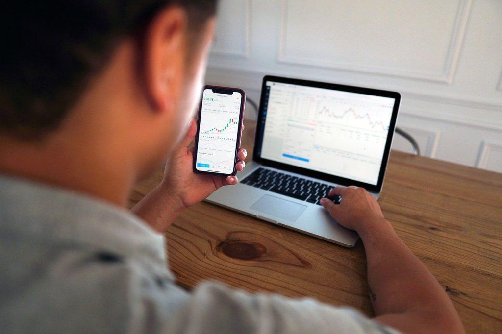 スマホとパソコンで投資をする男性